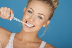 woman brushing her teeth because she believes in good oral hygiene