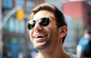 man in sunglasses smiling because he believes in gum disease prevention