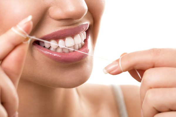 woman demonstrating how to properly floss in between teeth