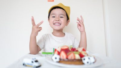 young boy at table about to lose his first tooth