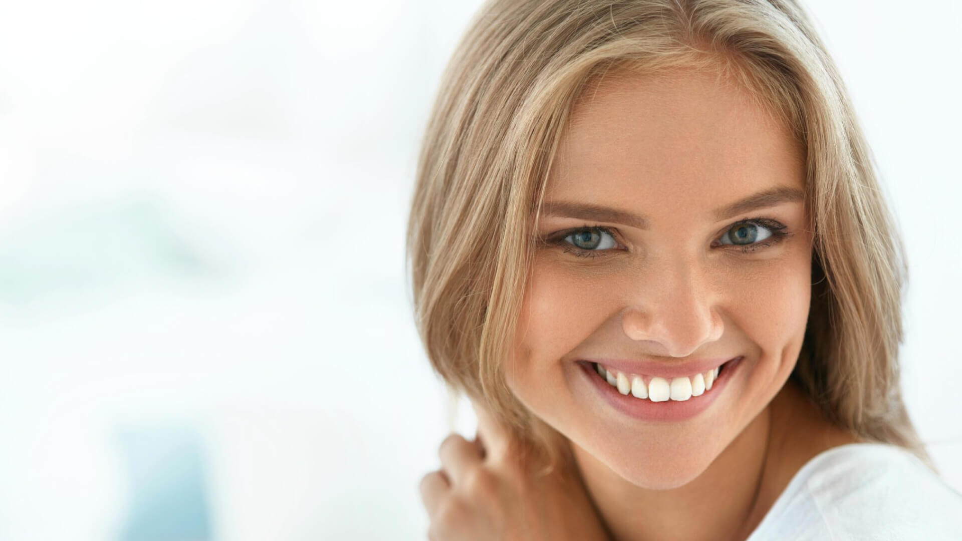 woman smiling after seeing a family dentist for teeth whitening