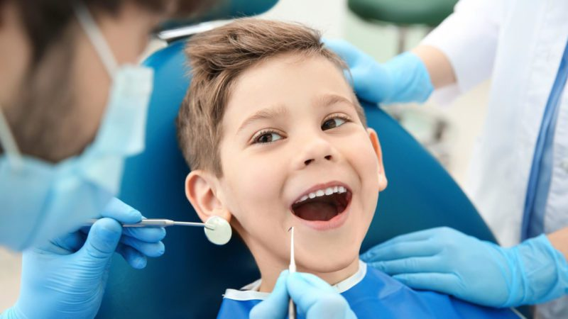 a child at the dentist celebrating national children 's dental health month