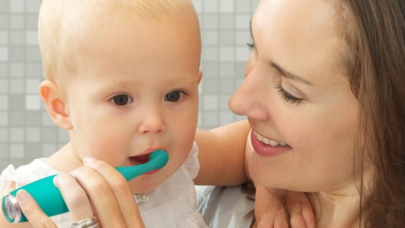mom brushing her childs teeth helping them get over their fear of the dentist