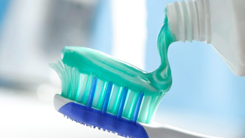 toothbrush getting flouride containing toothpaste squeezed onto it