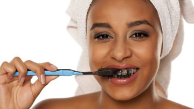 woman using activated charcoal teeth whitener