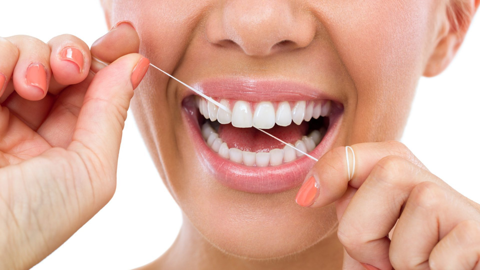 woman flossing her teeth while learning how to stop bleeding gums when flossing