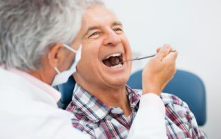 an older man seeing a local anderson indiana dentist to learn about brushing your teeth and alzheimers