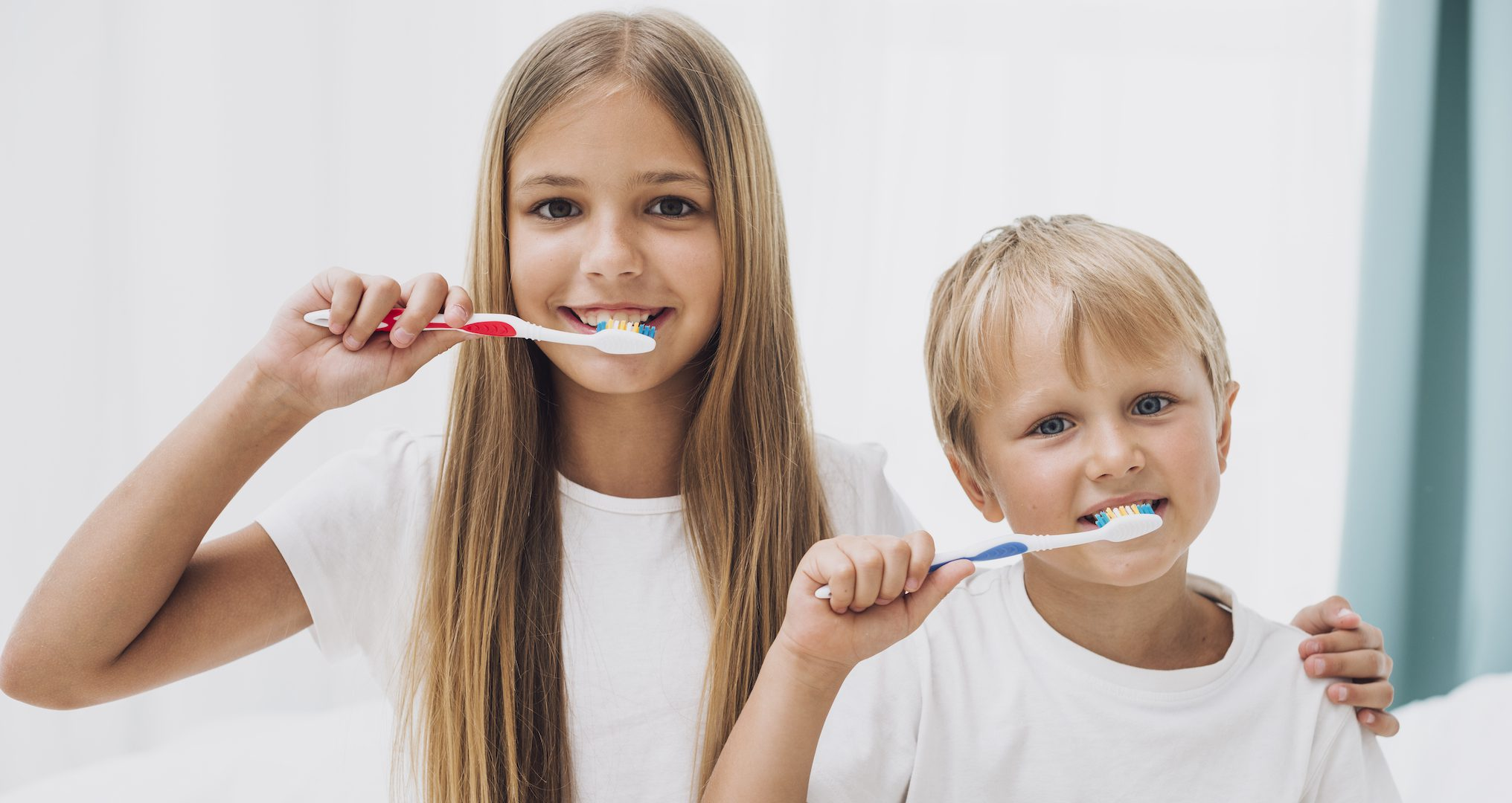 girl and boy brushing their teeth