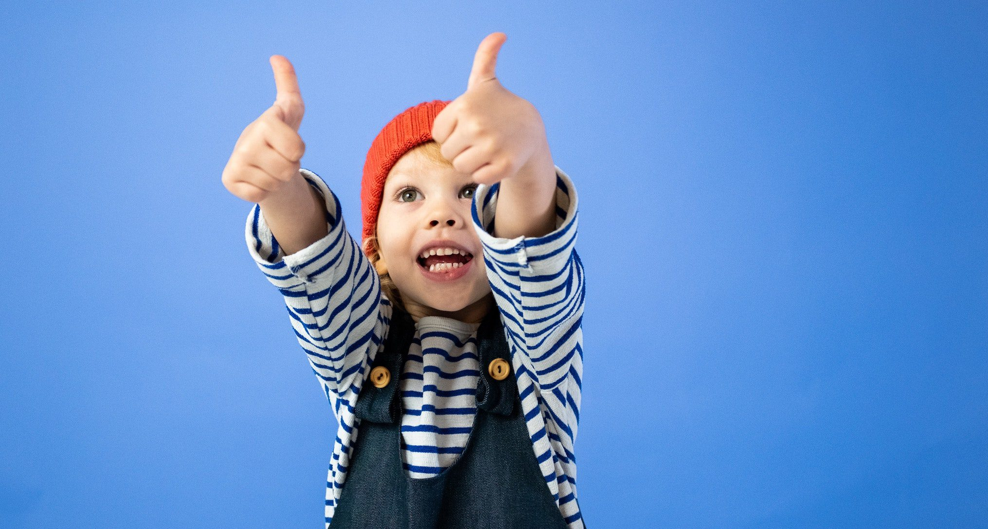 child giving two thumbs up